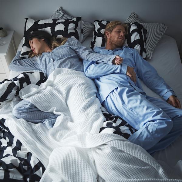 Egy pár egy fekete-fehér SKUGGBRÄCKA ágyneművel és egy VÅRELD ágytakaróval megvetett kétszemélyes ágyon mélyen alszik.