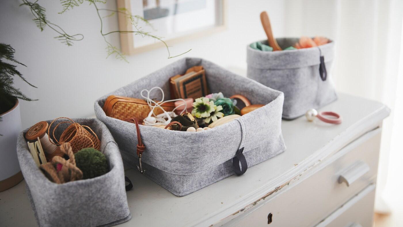 Egy régi, kopott fiókos szekrényen egy RAGGISAR textil kosárkészlet áll, a kosarakban mindenféle apró kis tárgy van.