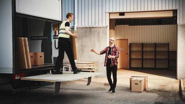 Egy szakállas és szemüveges férfi arra vár, hogy átvegyen egy tárgyat egy másik férfitól a teherautóhátulján.