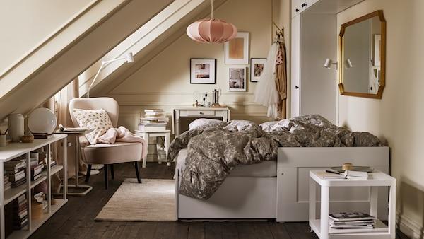 Egy szoba kihúzható fehér kanapéággyal, bézs/szürke ágyneművel, változatos tárolási megoldásokkal, egy bézs fotellel és egy rózsaszín függőlámpával.