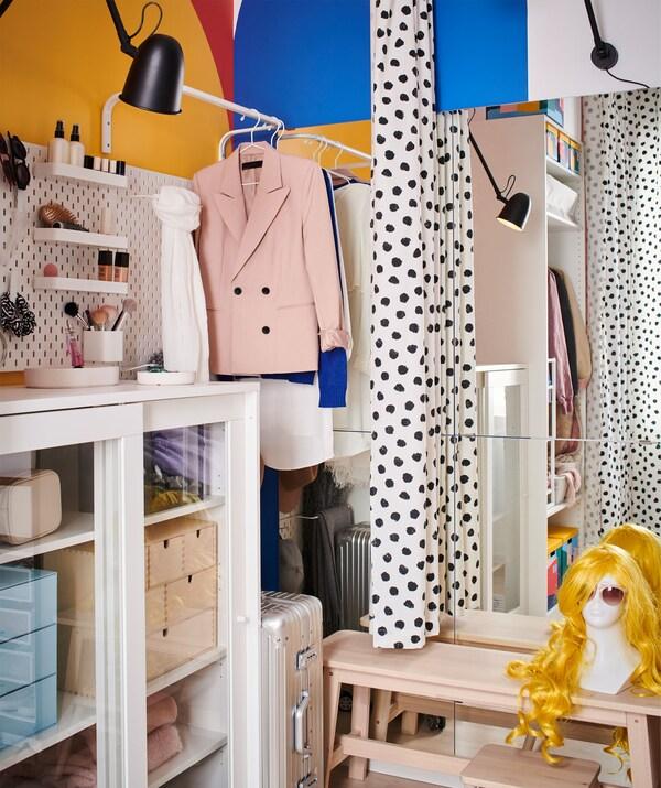 Egy szoba sarka, tárolókkal és ruhákkal a függöny egyik oldalán; pad, tükör és világítás a másikon.