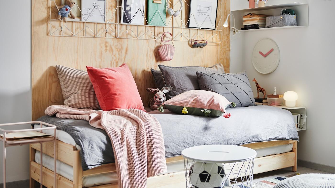 Egy UTÅKER rakásolható ágy sok párnával és textíliával, éjjeliszekrénnyel, tárolókkal és dekorációkkal körülvéve.