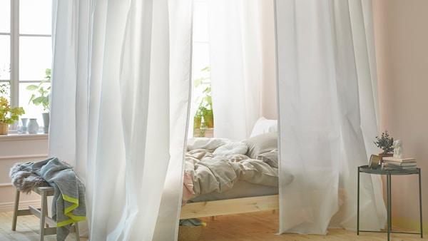 Egy világos hálószobában egy ágy áll az ablak mellett. Az ágy VIDGA függönysínere rögzített fehér függönyanyagból készült baldachinnal van körbevéve.