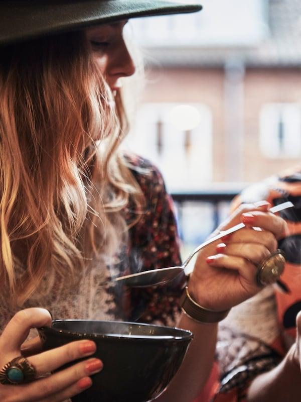 Egy vörös hajú nő kanállal meleg ételt eszik egy tálból. Kalapot és ékszereket visel.