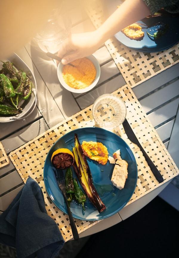 Ei hånd tar ei skje fra ei skål med saus omgitt av blå tallerkener med grillede grønnsaker på et trebord.