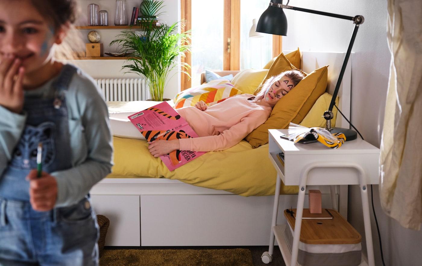 Ei jente sniker seg ut av et moderne soverom, etter å ha malt værhår og katteører i ansiktet til mora si, som sover i ei MALM seng.