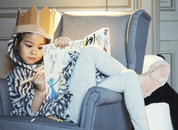 Ei jente som er kledd for å slappe av hjemme, ligger i en lenestol og tegner med ei papirkrone på hodet.