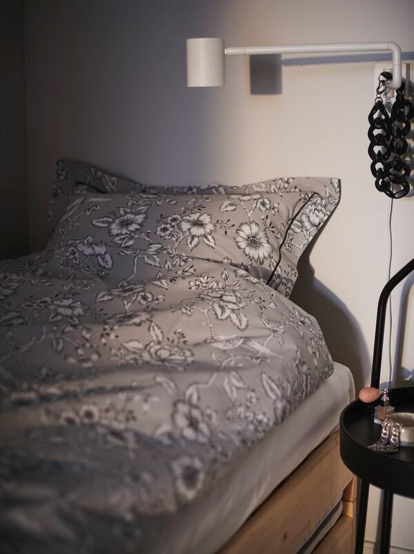 Ei seng med blomstret PRAKTBRÄCKA sengetøy. Ei NYMÅNE vegglampe står i lesestilling.