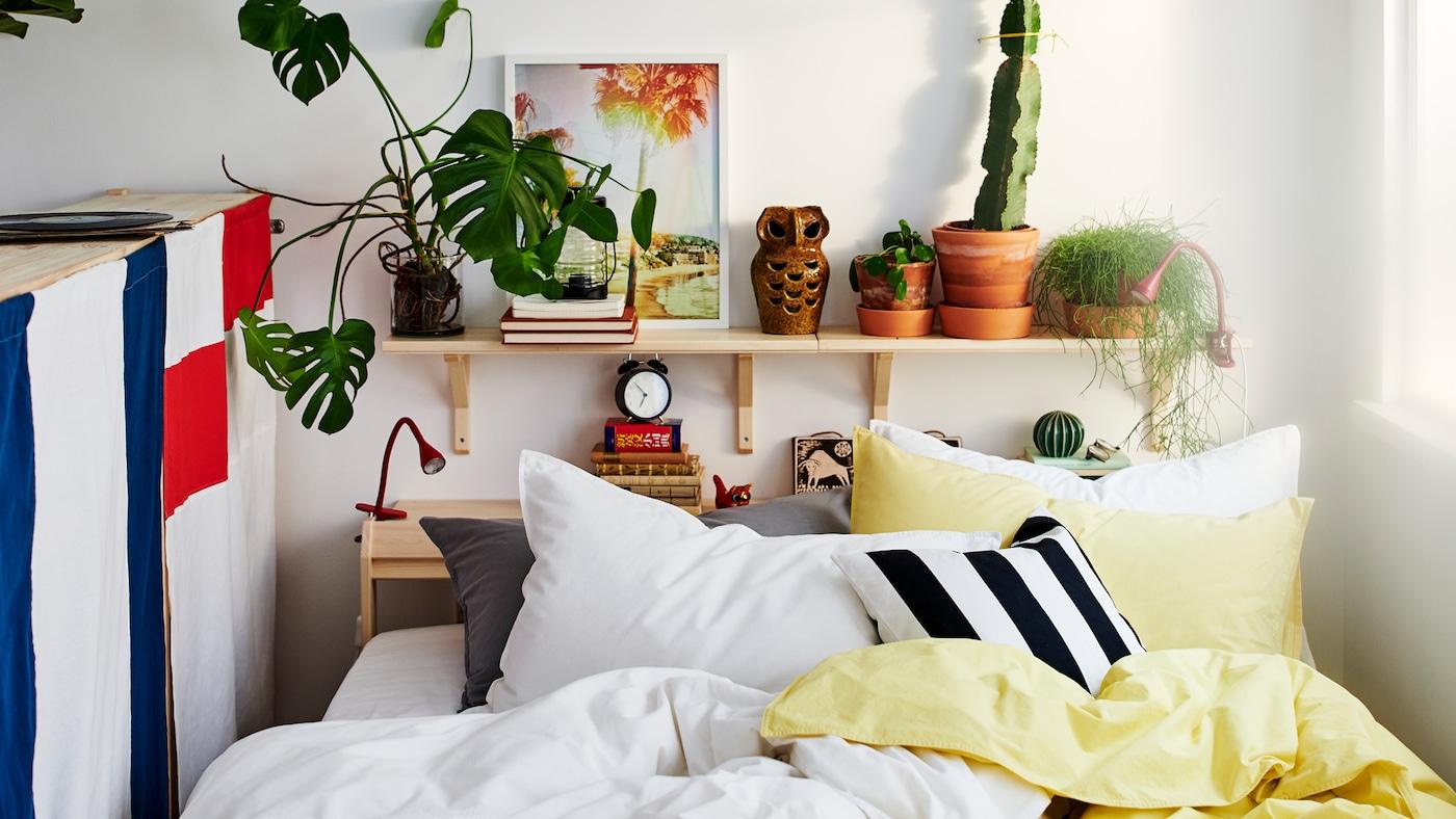 Ei seng mellom et vindu og baksiden av en oppbevaringsenhet med masse puter og gult, hvitt, svart og grått sengetøy.