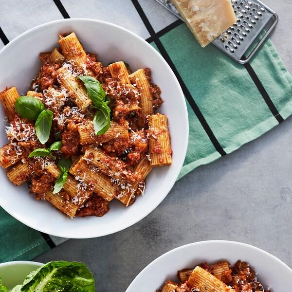 Ei skål pasta bolognese laget av VÄRLDSKLOK plantebasert hakk med fersk basilikum og revet parmesan på et kjøkkenhåndkle.