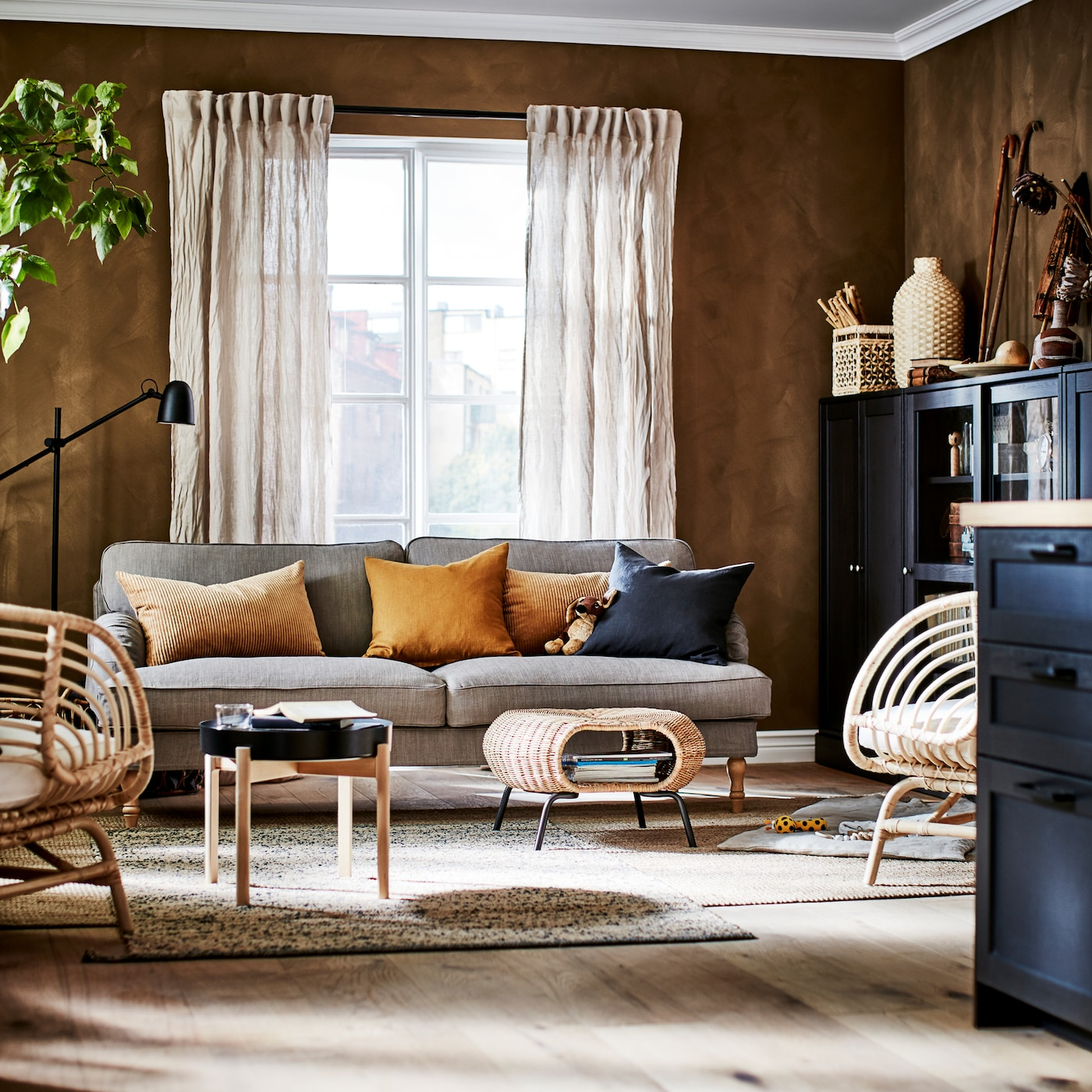 Ei stue med en gråbeige sofa, to jutetepper, to rottingstoler, beige lingardiner og mørkebrune skap.