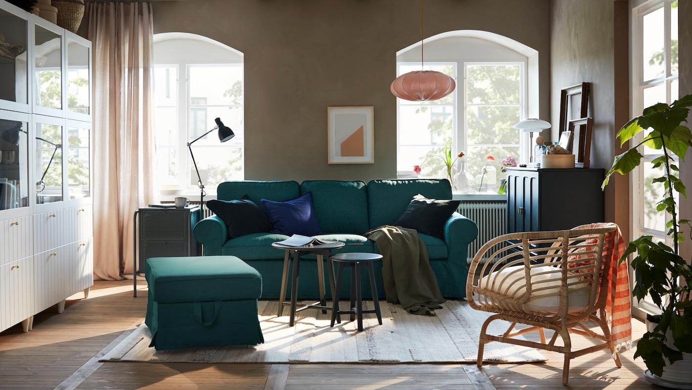Ei stue med sofa og fotskammel i mørk turkis, hvit oppbevaringskombinasjon og et mørkt, blågrønt skap.