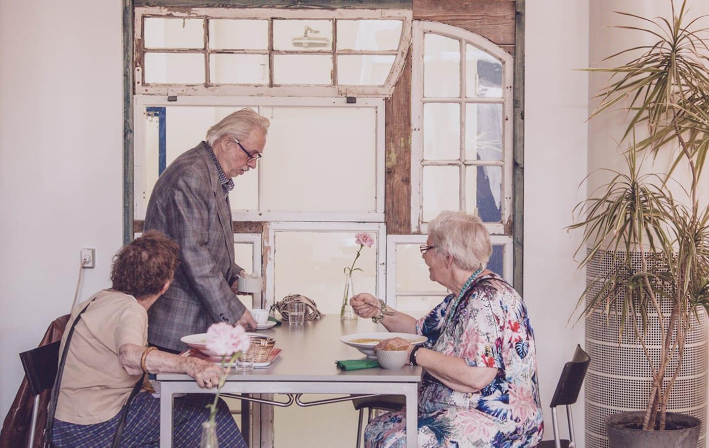 Ein älterer Mann & zwei ältere Damen sitzen an einem Tisch und nehmen eine Mahlzeit ein.