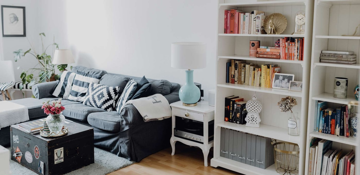 Ein äufgeräumtes Wohnzimmer mit einer grauen Couch und einem offenen weißen Schrank.