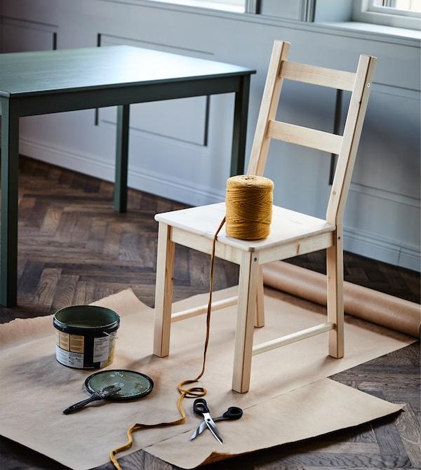 Ein alter Stuhl steht mit Farbe & Schnur bereit für seine Auffrischung