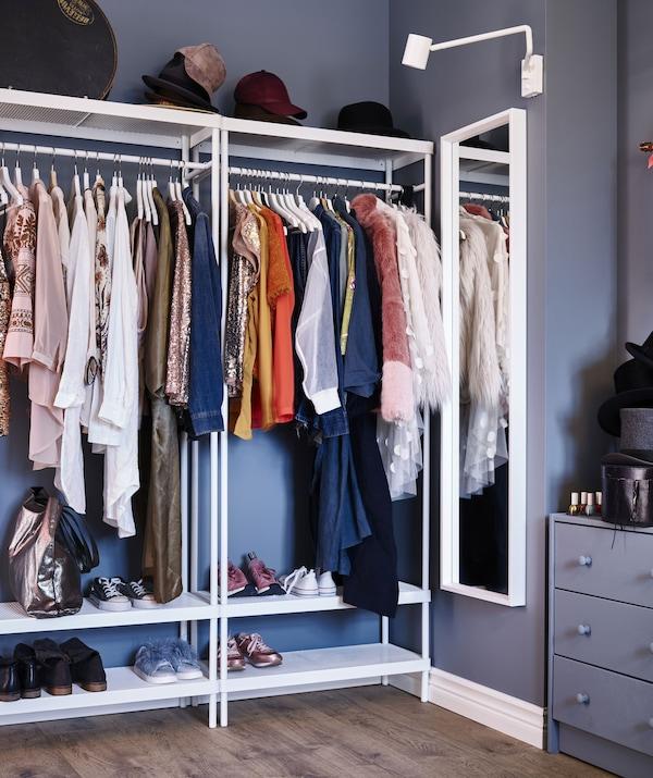 Ein Ankleidebereich mit einem NISSEDAL Spiegel, daneben sind zwei Kleiderständer mit Hemden, Kleidern und Schuhen zu sehen.