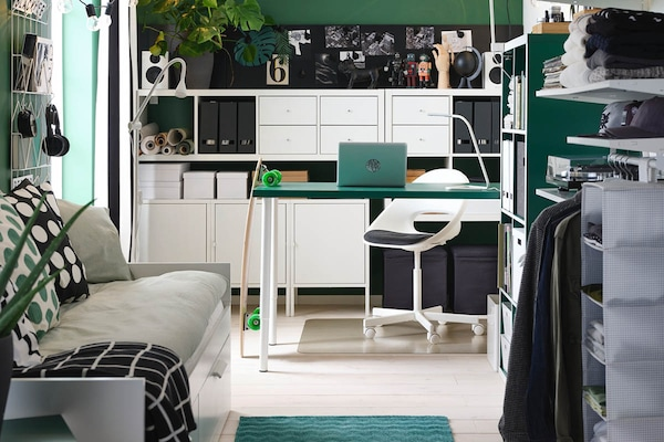 Ein Arbeitsplatz mit einem Schreibtisch mit grüner Tischplatte, einem Bürostuhl und Büroaufbewahrung