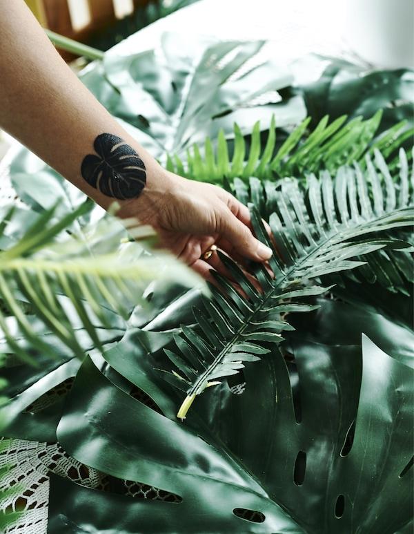 Ein Arm mit einer Tätowierung in Form eines Blattes hält SMYCKA Kunstblatt Monstera/grün.
