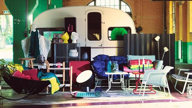 Ein Arrangement verschiedener Produkte der IKEA PS 2017 Kollektion bestehend aus klappbaren Sofas, Sesseln und Tischen, geräuschdämmenden Raumteilern, robusten Boxen, Kissen, Plaids, Leuchten und Vasen.