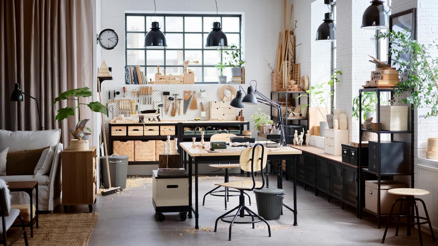 Ein Atelier im Industrial Style mit hohen Decken, Möbeln aus Holz und schwarzem Metall vor hohen Fenstern.
