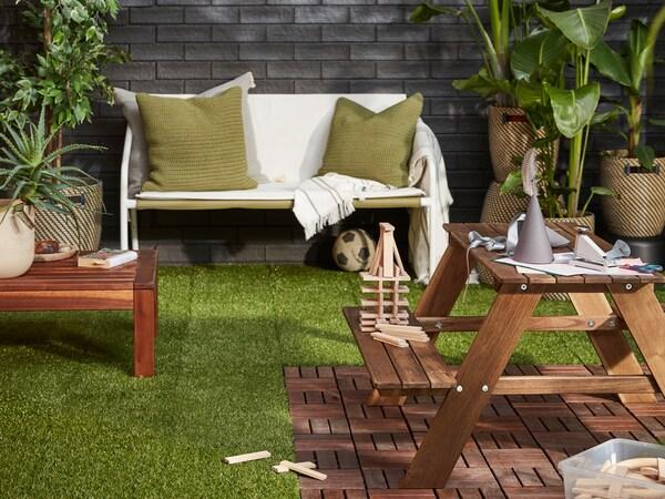 Ein Aussenbereich mit Bodenraster in zwei verschiedenen Oberflächen. Darauf sind Gartenmöbel zu sehen.