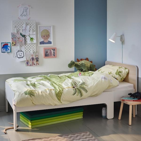 Ein ausziehbares Bettgestell mit Federholzrahmen in Weiß/Birke mit Bettwäsche mit Dinosauriermuster und einem Stofftierdino. Darunter liegt eine faltbare, grüne Gymnastikmatte.
