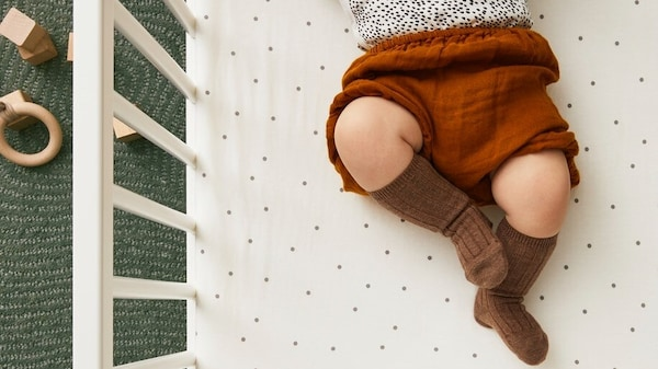 Ein Baby liegt schlafend auf einer farbenfrohen KLÄMMIG Babydecke, die Ärmchen sind ausgestreckt und liegen um den Kopf.