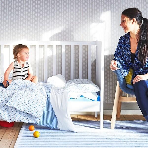 Ein Baby sitzt in einem Babybett und schaut eine Frau an