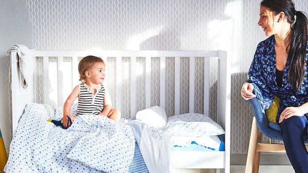 Ein Baby sitzt in einem Gitterbett von IKEA und schaut zur Seite