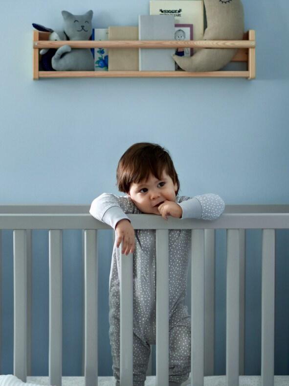 Ein Baby steht in einem Gitterbett