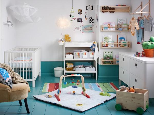 Ein Babyzimmer in Blau und Weiß, u. a. mit GULLIVER Wickeltisch in Weiß, einem weißen Babybett und einer Kommode.