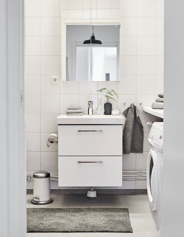 Ein Badezimmer in weißer und grauer Farbpalette, u. a. mit HÄREN Gästehandtüchern in Mittelgrau.