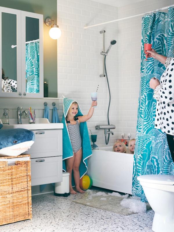 Ein Badezimmer mit drei Kindern, in dem sich drei Kinder in oder neben der Badewanne befinden. Ein Kind ist ein RÖRANDE Kapuzenhandtuch gehüllt und hält eine lustige Rede auf seine Mutter.