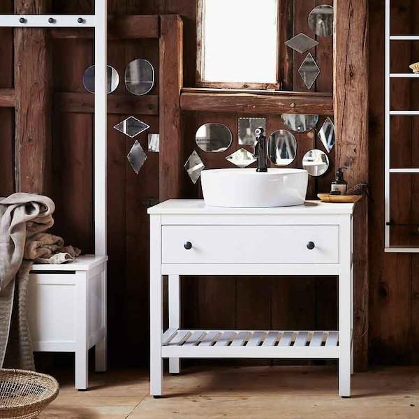 Ein Badezimmer mit dunklen Holzwänden mit mehreren Spiegeln in ungewöhnlichen Formen und HEMNES Badezimmermöbeln in Weiß.
