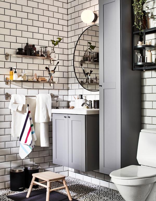 Ein Badezimmer mit grauen ENHET Badezimmermöbeln und zwei an der Wand montierten BROGRUND Glasböden für getrennte Aufbewahrung.