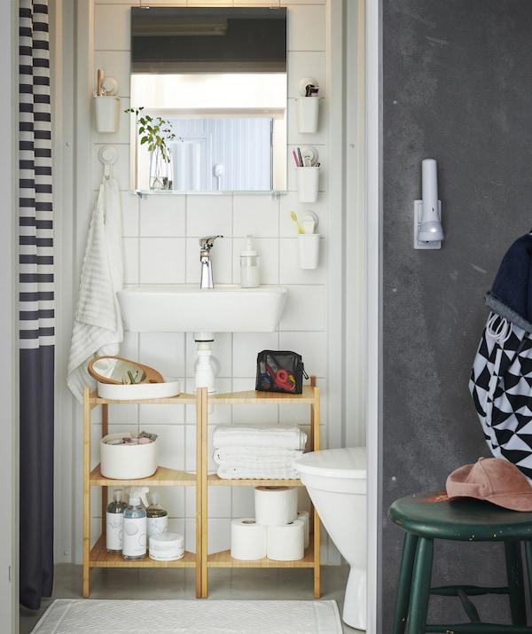 Ein Badezimmer mit RÅGRUND Waschbecken-/Eckregal aus Bambus unter dem Waschbecken und Zahnbürsten in an die Wand montierten Behältern.
