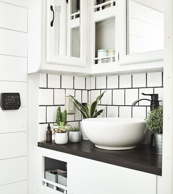 Ein Badezimmerbereich mit weißen Kacheln und SUCCULENT Pflanzen mit Übertopf grau