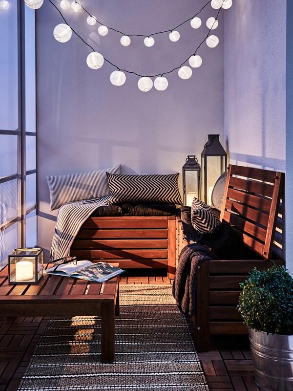 Ein Balkon mit einer ÄPPLARÖ Banktruhe und einem ÄPPLARÖ Tisch-/Hockerelement. Von oben hängen Lichterketten herab.