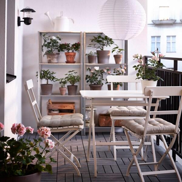 Ein Balkon mit weißem MÄLARÖ Tisch & weißen Klappstühlen, 2 Regalen & Pflanzen