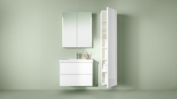 Ein beige gestrichener Raum, in dem nur ein Waschbeckenschrank, ein Spiegelschrank und ein Hochschrank in Weiss an der Wand befestigt zu sehen sind.