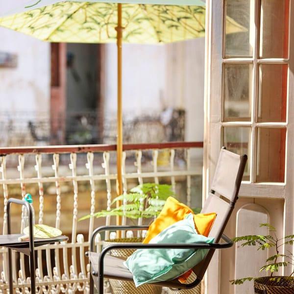 Ein bequemer Gartenstuhl mit Kissen auf einem Balkon. Ein Sonnenschirm spendet Schatten.