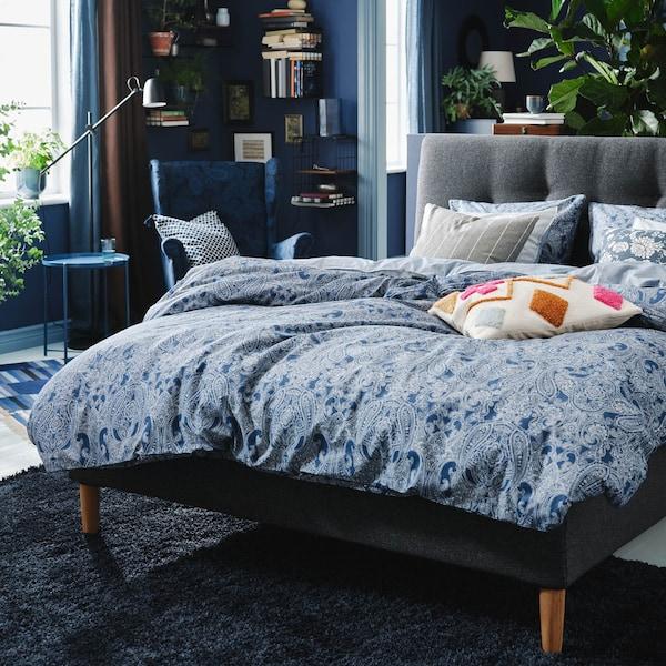 Ein Bett mit blauer Bettwäsche in der Mitte eines Raumes