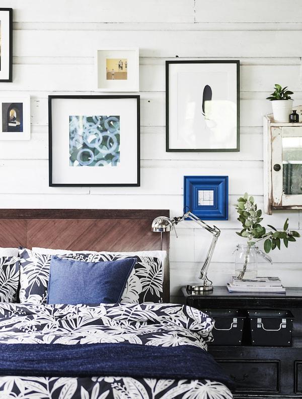 Ein Bett mit blauer und weißer Bettwäsche. Darüber ist eine Reihe von Bildern zu sehen.