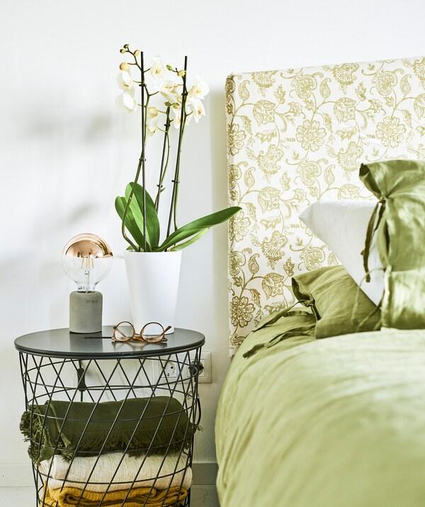 Ein Bett mit grüner Bettwäsche, daneben u. a. ein KVISTBRO Aufbewahrungstisch in Dunkelblau