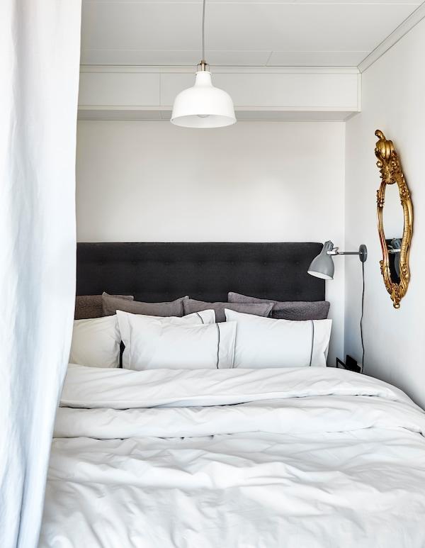 Ein Bett mit jeder Menge Kissen und dicken Decken in neutralen Farben