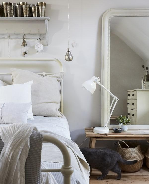 Ein Bett mit naturfarbenen Textilien, u. a. mit MATHEA Plaid weiss. Ausserdem läuft eine graue Katze durchs Bild.