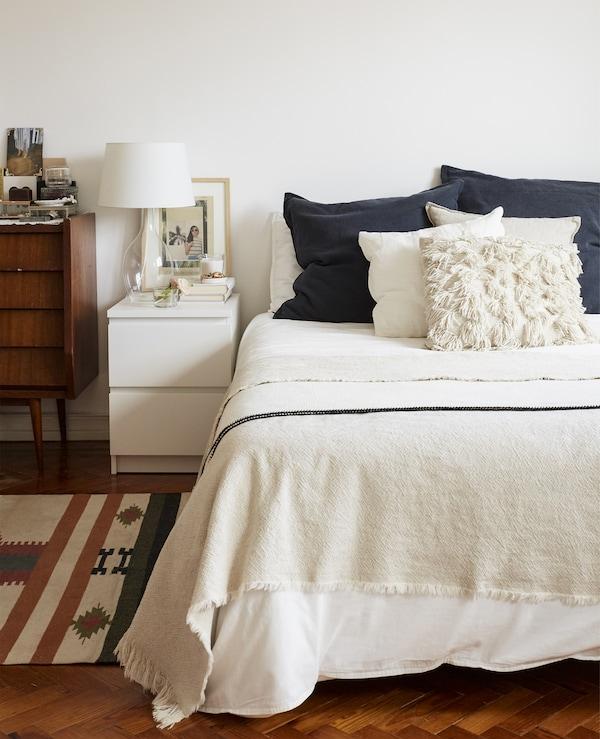 Ein Bett mit weißer Bettwäsche und blauen Kissen, einem modernen Ablagetisch und einem alten Schrank daneben.