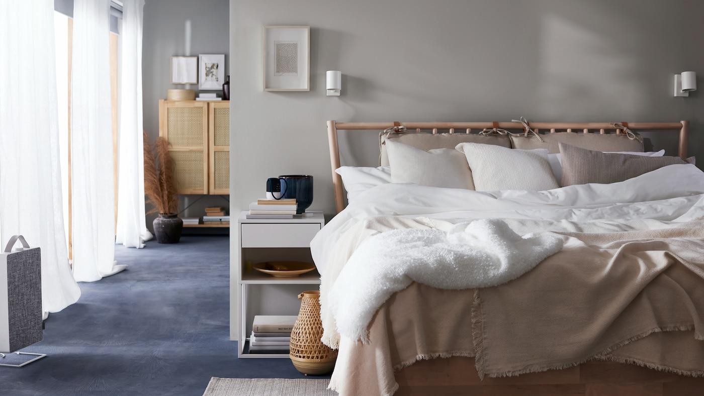 Ein Bettgestell mit weißer und beigefarbener Bettwäsche neben einem weißen Ablagetisch.