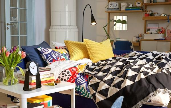Ein Bettsofa als Bett, Wohn- und Arbeitsbereich, u. a. mit einem TINGBY Beistelltisch auf Rollen und einem GULLKLOCKA Kissenbezug