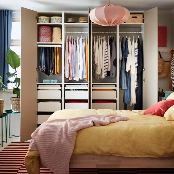 Ein BJÖRKSNÄS Bettgestell aus Birkenholz, gelbe Betttextilien, ein rotweißer Teppich und ein offener Kleiderschrank, in dem Kleidung auf Stangen, auf Böden und in Schubladen zu sehen ist.